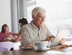 Older man using tablet computer in cafe